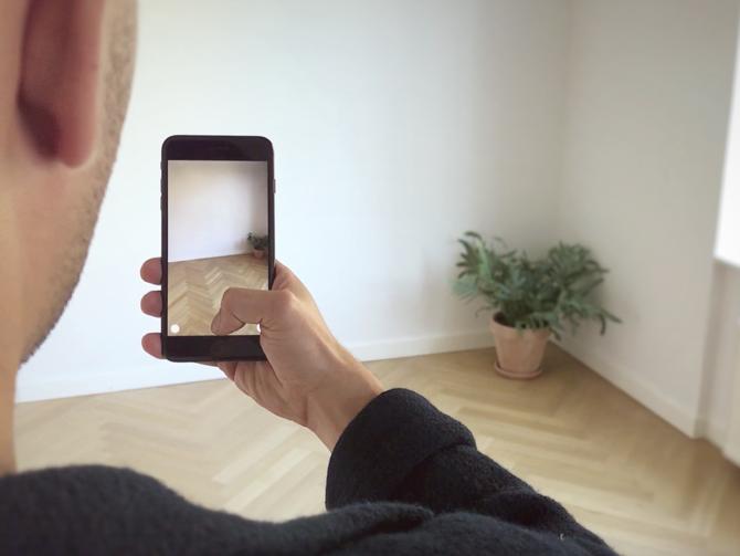 Uomo che tiene in mano il dispositivo mobile per sperimentare IKEA Place, un'applicazione AR per visualizzare i mobili