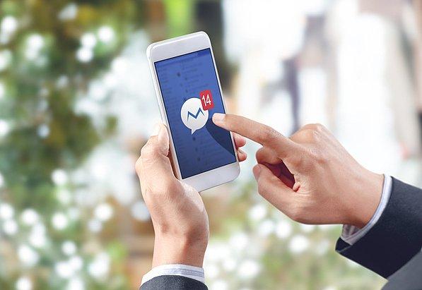 Un gestore di community social media apre l'app di messaggistica della sua piattaforma per rispondere ai messaggi follower.