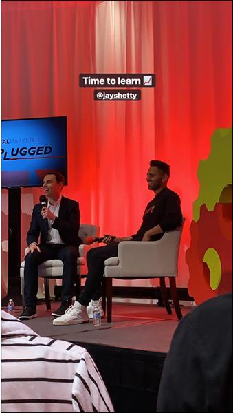 Jay Shetty sul palco parla in una conferenza di marketing