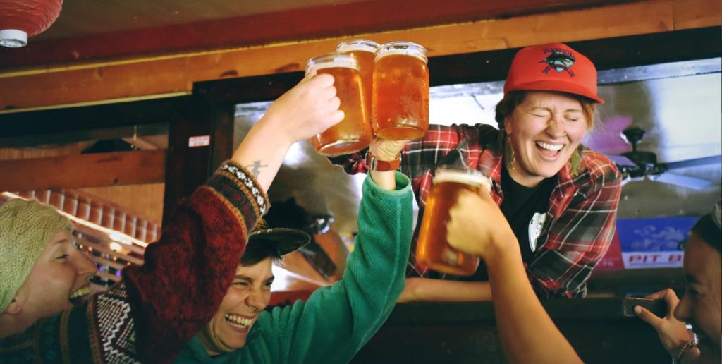 persone che tintinnano boccali di birra.