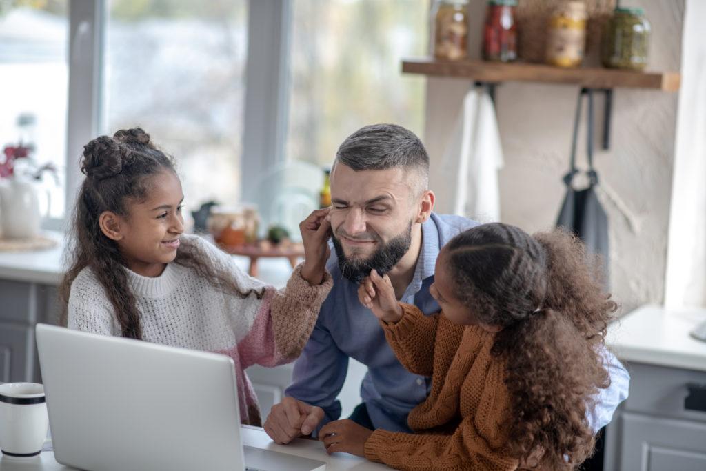 Figlie allegre dai capelli ricci che si divertono con papà mentre sta cercando di lavorare sul suo laptop.