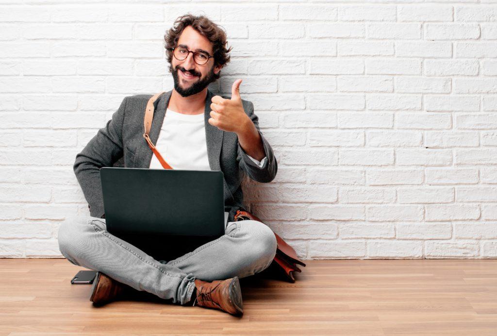 """Giovane uomo seduto sul pavimento con uno sguardo soddisfatto, orgoglioso e felice con i pollici in su, segnalando OK con una mano, inviando un positivo, """"va bene' messaggio."""